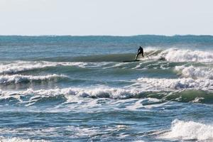 traje de surfista negro montando la ola foto