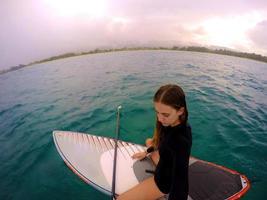 Niña sentada en una tabla de surf en Hawaii