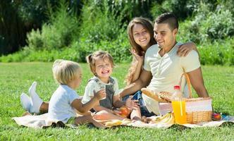 familia de cuatro teniendo picnic