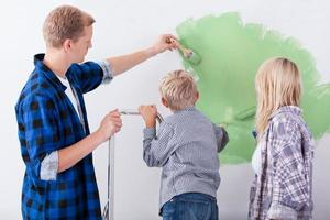 Family painting interior wall of home