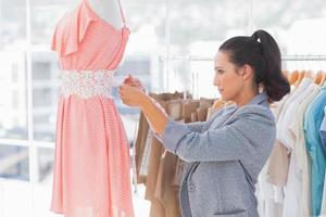 Pretty fashion designer measuring dress on a mannequin