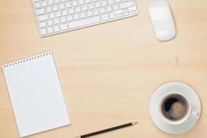 mesa de oficina con bloc de notas, computadora y taza de café