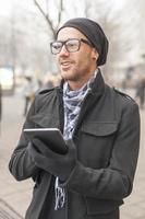 Man holdin i-pad tablet computer on street