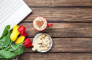 taza de capuchino con forma de corazón y computadora foto