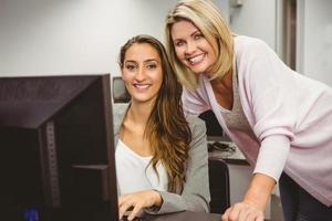 Profesor sonriente y estudiante detrás del escritorio en la computadora foto