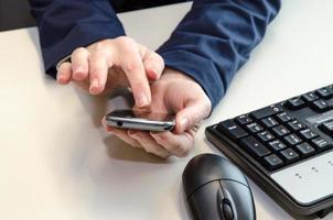 celular nas mãos, mouse e teclado
