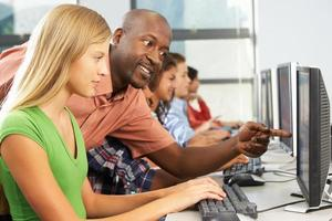 leraar die studenten helpt die bij computers in klaslokaal werken