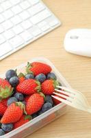 Lonchera saludable con mezcla de fresas y arándanos en la oficina foto