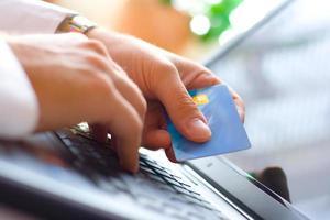 una persona que usa una computadora portátil y pago con tarjeta de crédito en línea foto