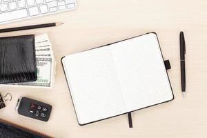 mesa de oficina con pc, suministros y dinero en efectivo foto