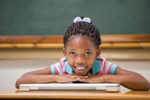 alumno sonriente sentado en su escritorio foto