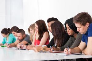 fila de estudiantes universitarios escribiendo en el escritorio