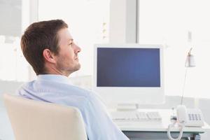 empresario sonriente sentado en su escritorio foto