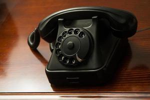 Old retro black telephone with round dial on wooden desk