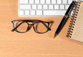 Close up Reading Eye Glasses on Businessman Wooden Table photo