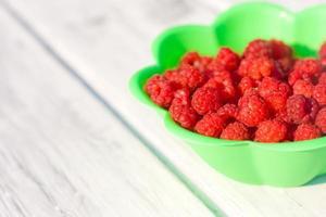 Fresh raspberry in plate on wooden rustic desk photo