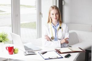 Young female doctor sitting at desk in clinic. photo