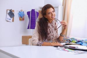 lachende vrouwelijke modeontwerper achter bureau