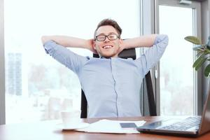 Businessman at desk with hands behind his head photo
