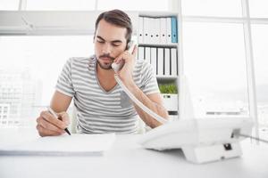 homme d'affaires décontracté écrit et téléphonant à son bureau
