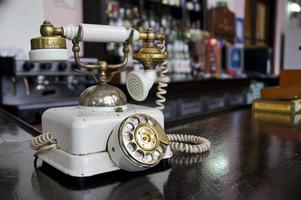 Old fashioned white candlestick phone on wooden desk
