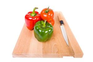 Chefs knive on wooden desk with fresh tomatoe and paprika photo