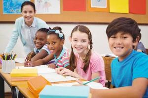 alumnos trabajando en sus pupitres en clase foto