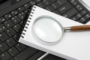 laptop, notebook y lupe en un escritorio
