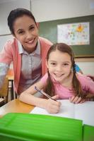 Pupil and teacher at desk in classroom photo
