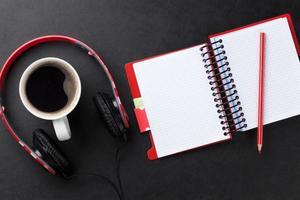 escritorio con bloc de notas, café y auriculares foto