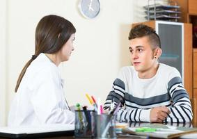 Teenager and doctor at desk in clinic