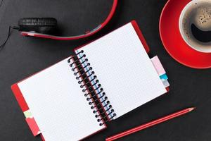 escritorio de oficina con bloc de notas, café y auriculares foto