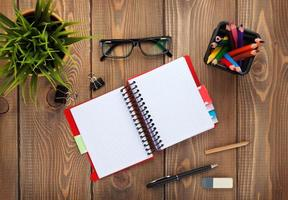 Office table with notepad, colorful pencils, supplies and flower photo
