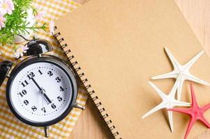 Brown diary and alarm clock.