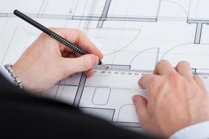 Businessman Working On Blueprint At Desk photo