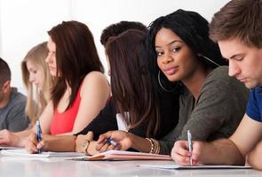estudiante seguro sentado con compañeros de clase escribiendo en el escritorio