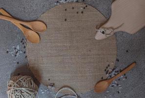 cucharas de madera, tabla de cortar y ovillo en el fondo de piedra foto