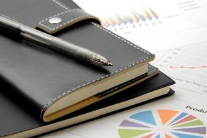 Personal organizer and pen on business material photo