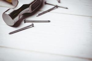 martelo e pregos dispostos na mesa