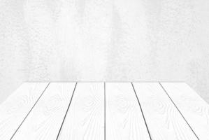 Empty white wooden table over white cement wall. photo