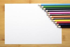 Blank paper and colorful pencils on the wooden table.