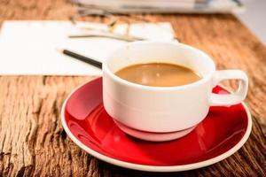 Taza de café y material de oficina en la mesa de madera vieja foto