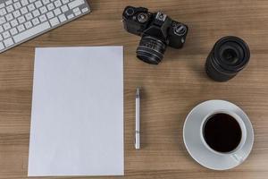 desktop met camera blanco vel en koffie