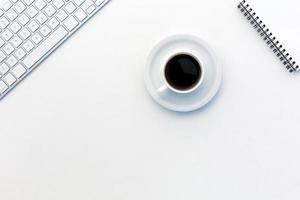 Vista de escritorio blanca de oficina electrónica de negocios y taza de café foto