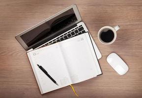 Bloc de notas, laptop y taza de café en la mesa de madera