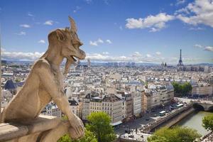 Notre Dame: Chimera (demon) overlooking Paris skyline a summer day