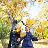 Family playing with autumn leaves photo