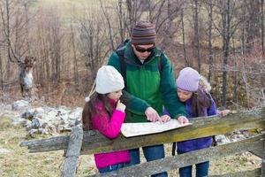 Family in nature looking at map photo