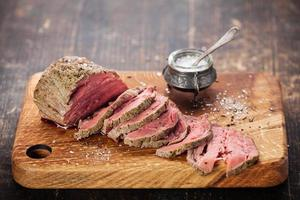 Sliced roast beef with salt in pot on wooden chopping board
