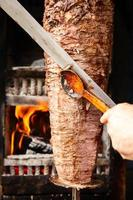 Doner meat being sliced from rotating spit photo